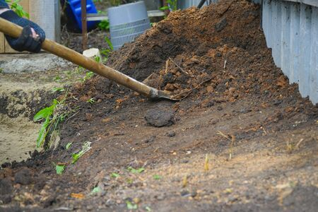 A worker in gloves digs the ground with a shovel