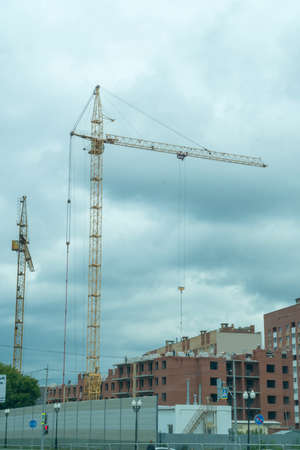 A crane on a construction site against a cloudy sky 免版税图像