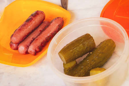 Grilled sausages and pickles in plastic dishes. Disposable tableware