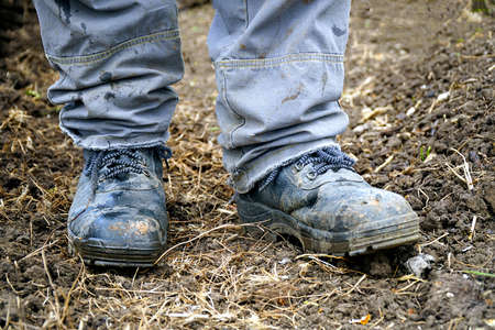 Workers feet in dusty boots. A man in overalls and work boots. Work clothes