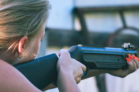 The girl holds a rifle and takes aim. Zdjęcie Seryjne