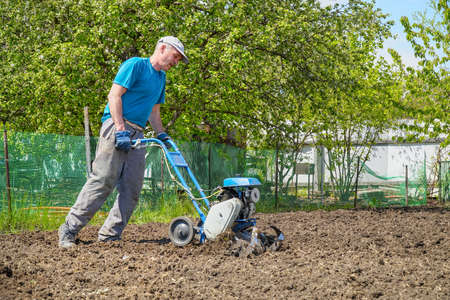 A man cultivates the soil in the garden using a motor cultivator