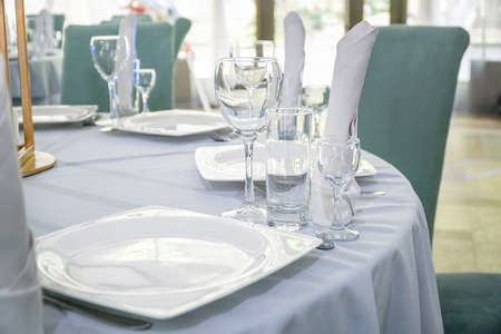 The table in the restaurant is served for lunch. On a table with a white tablecloth, empty wine glasses, a plate, napkins. Selective focus