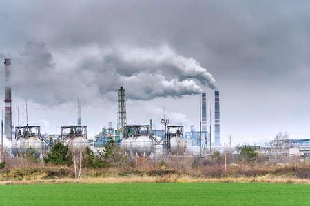 View of a chemical plant with Smoking chimneys against a dark cloudy dirty sky