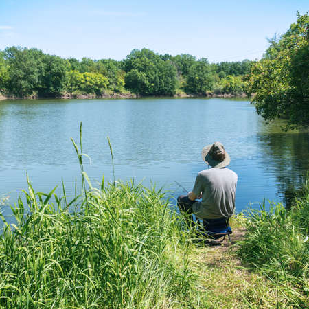 A fisherman in a hat is fishing on a forest lake or river Zdjęcie Seryjne
