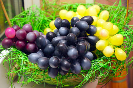 Bunches of artificial grapes on a plate