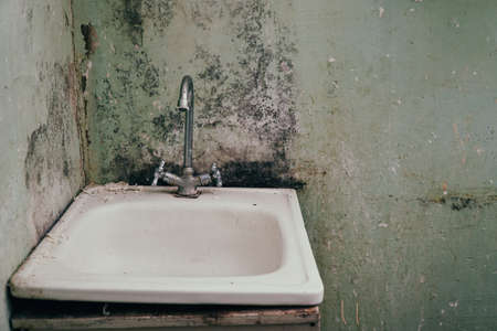 An old sink with a faucet on the background of dirty walls