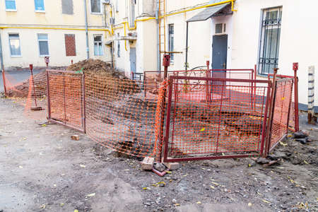 Pile of soil behind the fence at the entrance of the house. Utilities have dug a hole and are repairing sewers