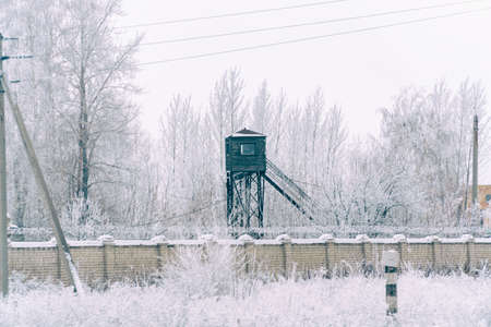 Prison tower at the fence with barbed wire. in winter in the snow Soft focus