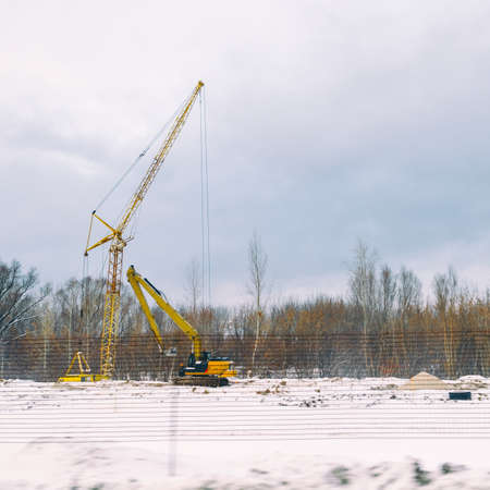 Lifting construction crane on a Construction site in a field near a forest in the winter season