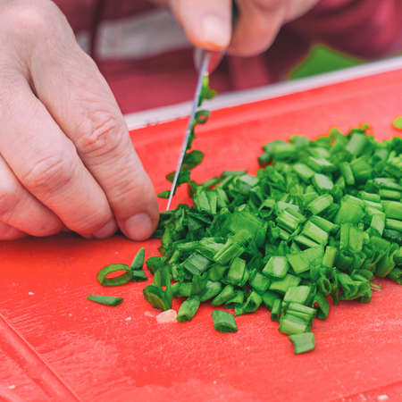 A woman cuts green onions with a knife. Selective focus