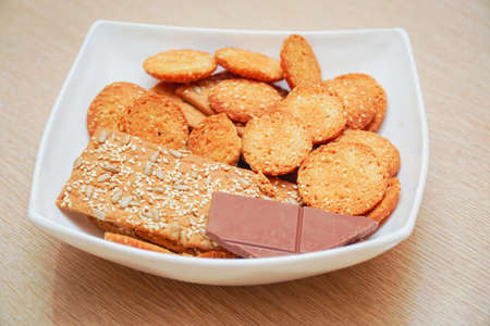 Cookies and a dark chocolate bar on a white plate