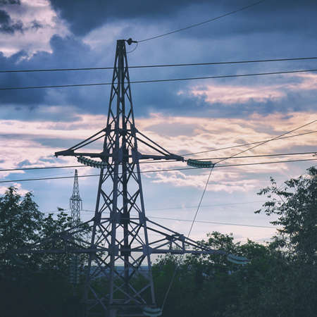 Silhouette of a high-voltage power line tower against a cloudy sky in the evening