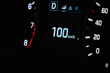 Speedometer in the car on the dashboard. The cars speedometer shows 100 mph
