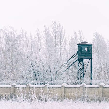 Prison tower at the fence with barbed wire. in winter in the snow Soft focus Standard-Bild