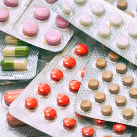 Different colored tablets and capsules packed in blisters.