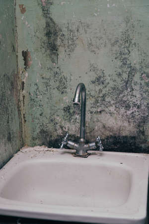Old sink with a faucet on the background of dirty walls