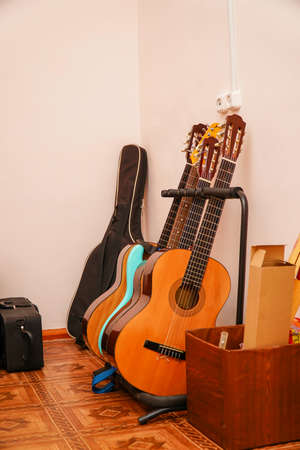 Several acoustic guitars on a stand in room