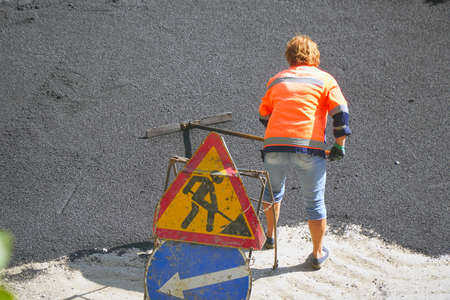 Female worker during asphalting road. Heavy female manual labor in construction