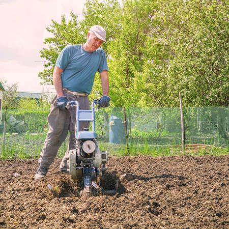 Man cultivates the soil in the garden using a motor cultivator - tiller Stock fotó