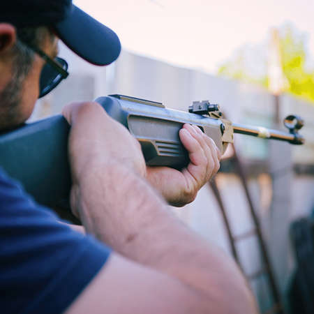 A man with a beard, a cap and dark glasses holds a rifle and takes aim