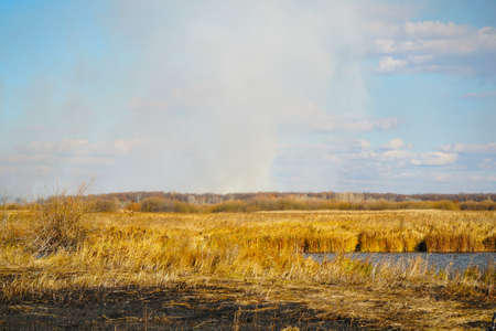 Smoke from a forest fire rises into the sky onsunny autumn day Stock fotó