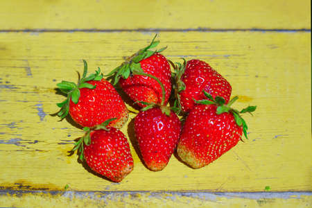 Red strawberries on old yellow wooden table Stock fotó