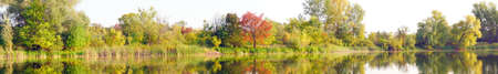 Panoramic view of the autumn forest with yellow and red foliage and a beautiful lake against the background of light sky Фото со стока