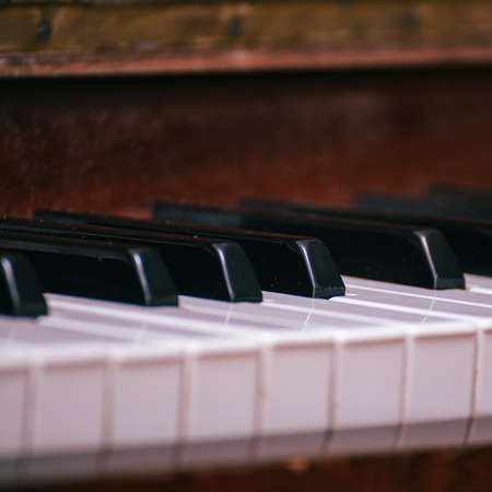 A fragment of the keyboard of an old piano. Black and white keys of an old piano Фото со стока