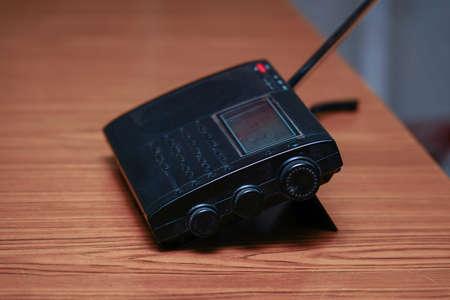 Black analog radio receiver on wooden table Фото со стока