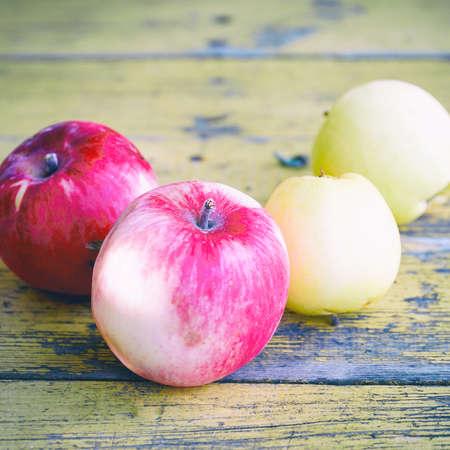 Ripe apples on old yellow garden table Фото со стока