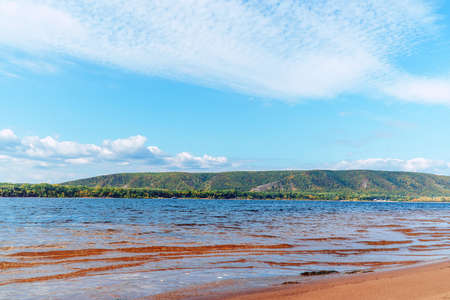 Big Volga river against the background of blue cloudy sky. On opposite bank of the Zhiguli Mountains Фото со стока