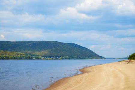 Sandy shore of the big Volga river against the background of a cloudy sky. On the opposite bank of the Zhiguli Mountains