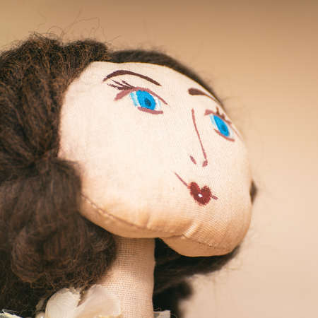 The face of a homemade rag doll with blue eyes. Portrait of a rag doll Фото со стока