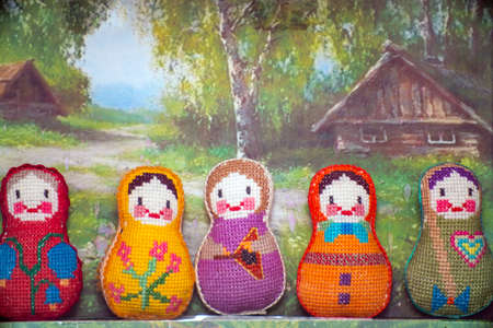 Knitted doll toys stand in a row on a rustic background Фото со стока