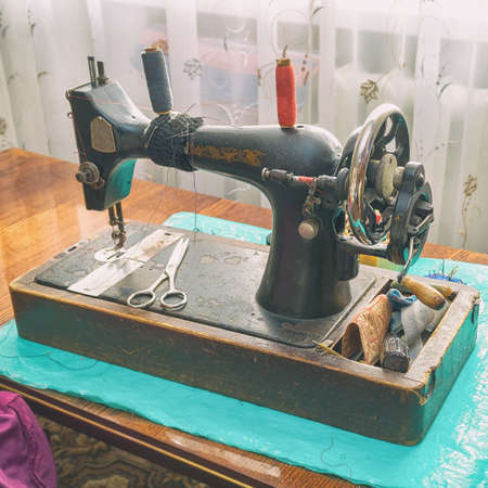 Vintage sewing machine on the table Фото со стока