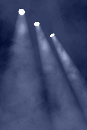 Three spotlights shining through a smokey haze for an interesting background photo