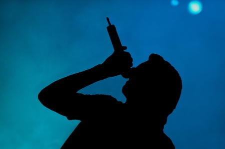 silhouetted: Singer on stage silhouetted against a rich blue background Stock Photo