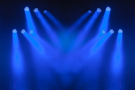 Multiple blue LED spotlights with criss-crossing beams lighting an empty stage.
