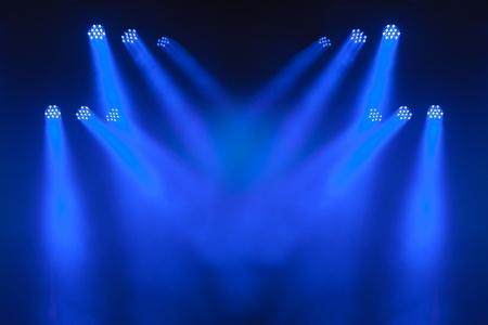 pallino: Pi� faretti LED blu con incrociando fasci di illuminare uno stadio vuoto.