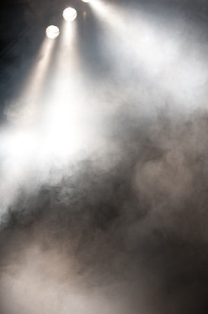 Spotlights shining downwards through a haze of smoke to an empty stage
