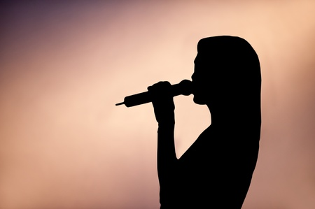 vocalist: Silhouette in profile of a woman singer holding a microphone to her mouth with copyspace
