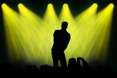 singing silhouette: Silhouette of a man singing on stage to an audience under spotlights