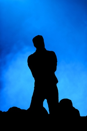 the vocalist: Silhouette of a man singing on stage in front of an audience against a blue background