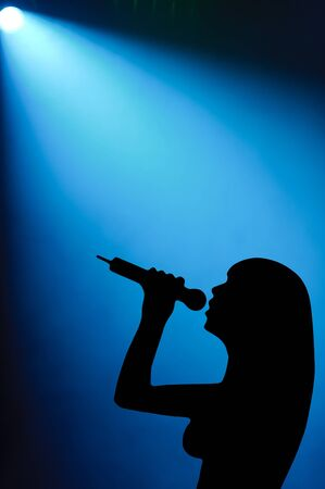 singer silhouette: Silhouette of a woman vocalist singing into a microphone under a spotlight Stock Photo