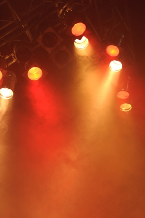 stage lighting: Bright spotlights shining down on to an empty stage creating a deep orange red misty or smokey glow