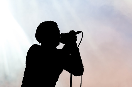amplify: Single singer holding a microphone to his lips sideways in silhouette
