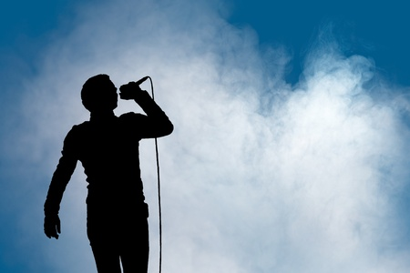 A single man sings into a microphone at a concert with atmospheric foggy background for copyspace