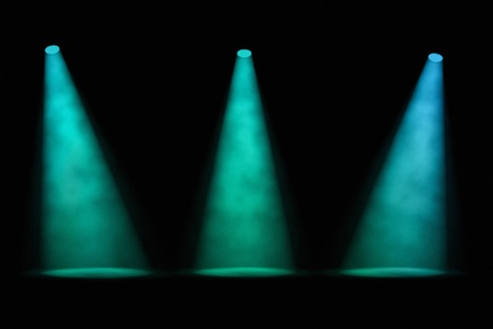 three angled: Three equally spaced separated smoky blue-green spotlight beams shining down onto an empty stage on a dark background