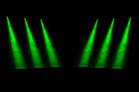 three angled: Six green angled spotlight beams shining down onto an empty stage in two rows of three with a dark foggy background Stock Photo